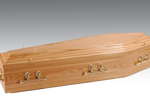 Oak veneered coffin with profiled features to coffin sides, fitted with plastic handles and a standard interior.
