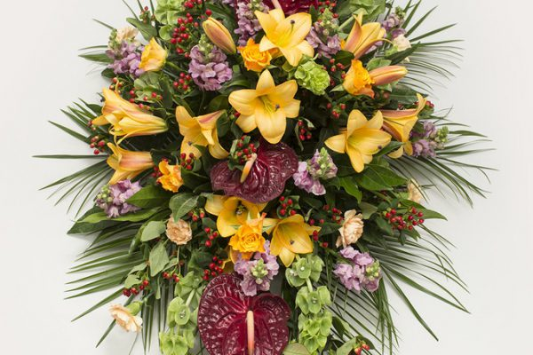 Lilies, Bells of Ireland, Roses, Carnations, Anthurium, Hypericum Berries and greenery make for a more contemporary style coffin spray. From €175.