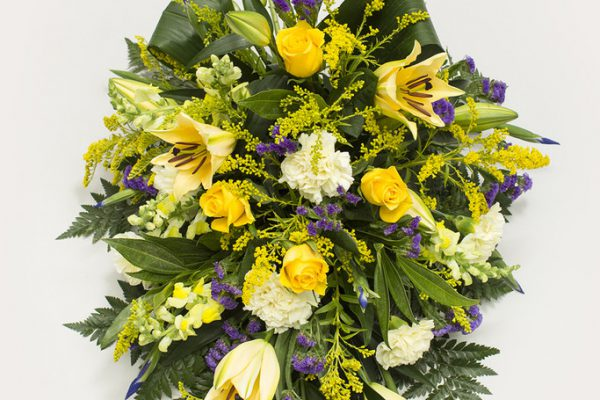 An arrangement of Lilies, Roses, Stocks, Solidagos and Carnations highlighted with Blue Status and set against a backdrop of fresh greenery. From €120.